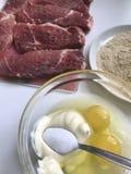 Morceaux de mensonge de viande sur la planche à découper À côté du récipient sont les ingrédients pour la pâte lisse : mayonnaise Photo libre de droits