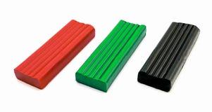 3 morceaux de pâte à modeler rouges, verts et de noir d'isolement Images libres de droits