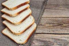 Morceaux de pain blanc sur renvoyer sur une vieille table en bois Image stock