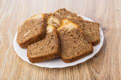 Morceaux de petit gâteau dans le plat blanc sur la table Image stock