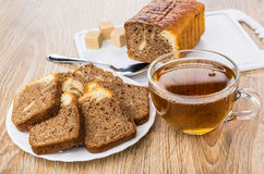 Morceaux de petit gâteau dans le plat blanc, tasse de thé Photographie stock libre de droits