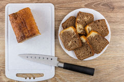 Morceaux de petit gâteau dans le plat, la planche à découper et le couteau blancs Photographie stock libre de droits