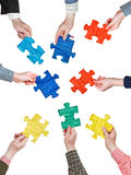 Morceaux de puzzle dans des mains de personnes en cercle Photo stock