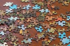 Morceaux de puzzle répandus au sujet d'une table Image stock