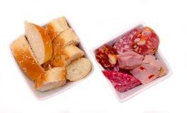 Morceaux de salami et de tranches de pain dans des cuvettes d'en haut Image libre de droits