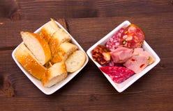 Morceaux de salami et de tranches de pain dans des cuvettes sur le bois d'en haut Photographie stock