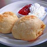 2 morceaux de scone avec la confiture de crème et de fraise Photo stock