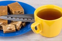 Morceaux de sorbet avec l'arachide et les raisins secs, couteau, thé photographie stock libre de droits