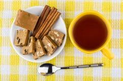 Morceaux de sorbet, bâtons de cannelle dans la soucoupe, tasse de thé photos stock
