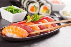 Morceaux de sushi avec des baguettes Image stock