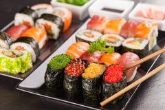 Morceaux de sushi avec des baguettes Photographie stock libre de droits