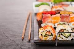 Morceaux de sushi avec des baguettes Photos stock