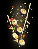 Morceaux de sushi congelés dans le ciel sur le fond noir Photos stock