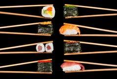 Morceaux de sushi en baguettes Photographie stock libre de droits