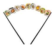 Morceaux de sushi placés entre les baguettes sur le fond blanc Photos libres de droits
