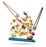 Morceaux de sushi placés entre les baguettes sur le fond blanc Photographie stock