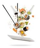Morceaux de sushi placés entre les baguettes sur le fond blanc Images libres de droits