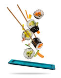 Morceaux de sushi placés entre les baguettes sur le fond blanc Photo stock
