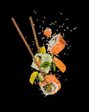 Morceaux de sushi placés entre les baguettes sur le fond noir Images libres de droits