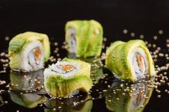 Morceaux de sushi sur le fond noir Images stock