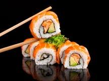 Morceaux de sushi sur le fond noir Photographie stock libre de droits