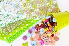Morceaux de tissu avec un modèle, différents boutons, seau vert Images libres de droits