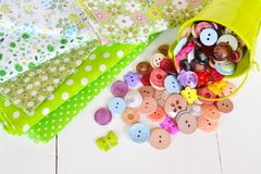 Morceaux de tissu dans des modèles de point de fleur et de polka Peu de seau vert avec les boutons colorés décoratifs Image stock