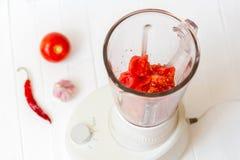 Morceaux de tomate dans un mélangeur Tomate, tomate, poivre, mensonge d'ail sur un fond en bois Image stock
