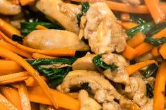Morceaux de viande de poulet faisant frire avec les carottes coupées en tranches photographie stock libre de droits