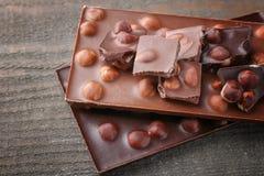 Morceaux et barres cassés de chocolat avec la noisette Image libre de droits