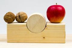 Morceaux géométriques en bois avec des pommes et des noix Image stock
