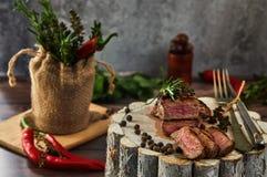Morceaux moyens juteux de bifteck de boeuf d'oeil de nervure dans une casserole sur un conseil en bois avec une fourchette et un  image stock