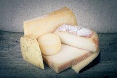 Morceaux principaux et divers de fromage sur une table en bois teinté Images stock