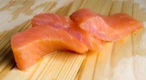 Morceaux saumonés sur le conseil photos stock