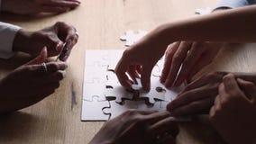 Morceaux se reliants de personnes multi-ethniques de vue de plan rapproché de puzzle de puzzle banque de vidéos