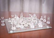 Morceaux sur l'échiquier. L'ensemble d'échecs figure sur le conseil jouant. Échecs en verre Image stock