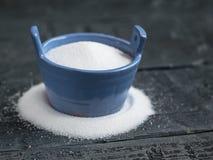 Morcellement d'amende de sel de mer le bleu de dispositif trembleur sur une table rustique Photographie stock libre de droits