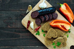 Morcillo Spanish black pudding, blood sausage, cutting slices, black rye bread in a heart shape, pepper, garlic Stock Photo