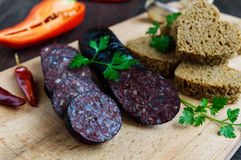 Morcillo Spanish black pudding, blood sausage, cutting slices, black rye bread in a heart shape, pepper, garlic Stock Photos