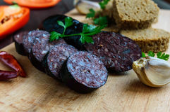 Morcillo Spanish black pudding, blood sausage, cutting slices, black rye bread in a heart shape, pepper, garlic Stock Photography