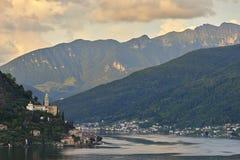 Morcote Schweiz - Juni 4, 2017: Sikt över sjön Lugano till staden Morcote i Ticino, Schweiz och kyrkan av Santa Maria de Royaltyfri Bild