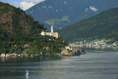 Morcote Schweiz - Juni 4, 2017: Sikt över sjön Lugano till staden Morcote i Ticino, Schweiz och kyrkan av Santa Maria de Royaltyfri Fotografi