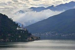 Morcote, Suíça - 4 de junho de 2017: Vista sobre o lago Lugano à cidade Morcote em Ticino, em Suíça e na igreja de Santa Maria de Fotografia de Stock Royalty Free