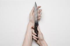 Mord- und Halloween-Thema: Die Hand eines Mannes, die für ein Messer, eine menschliche Hand hält ein Messer lokalisiert auf einem stockfotos
