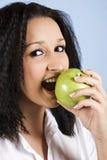 Mordedura de la mujer joven una manzana verde Imagen de archivo libre de regalías
