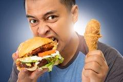 Mordedura del hombre joven su hamburguesa grande Foto de archivo libre de regalías