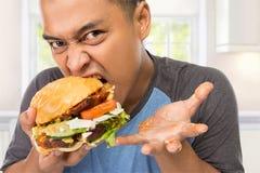 Mordedura del hombre joven su hamburguesa grande delicioso Fotos de archivo libres de regalías