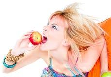 Mordedura hermosa de la mujer joven una manzana Foto de archivo