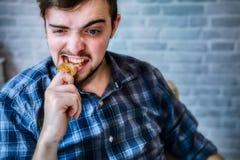 Mordeduras del hombre de negocios un bitcoin de oro para la autenticidad de los controles con sus dientes foto de archivo