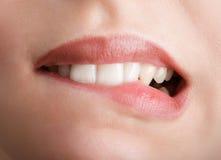 Morder sus dientes rojos de los labios Foto de archivo